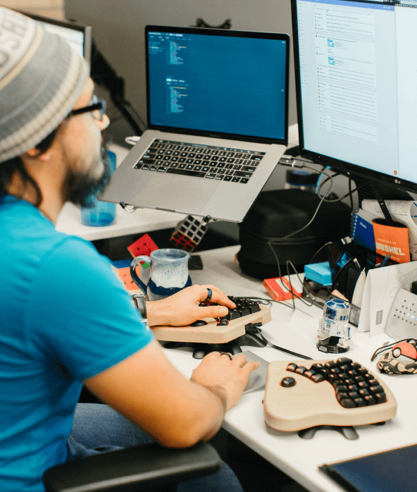 male developer working at his desk on a unique keyboard