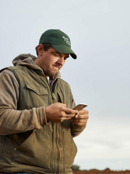 Farmer using Bushel Mobile application on phone
