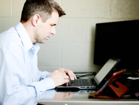 man working at a laptop computer